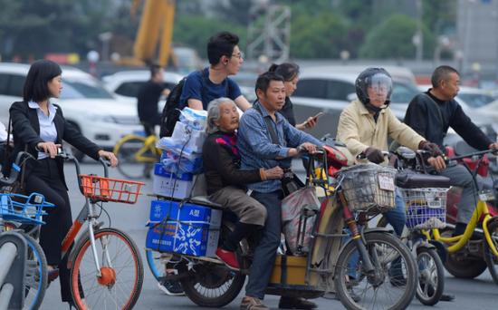 带92岁母亲上班   拖着货物,牵着老母